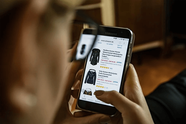 orang sedang ingin belanja online pakaian dengan ponsel